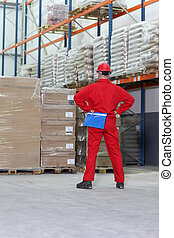 worker checking inventory - worker in red uniform checking...