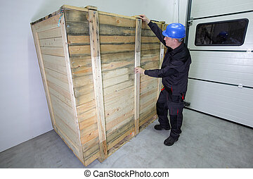 worker checking large wooden box