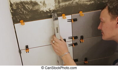 Worker checking level laying tiles on the wall