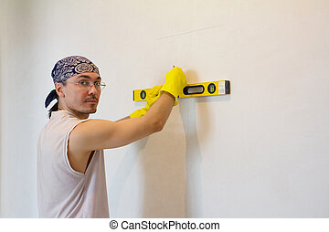 Worker checking level of house wall