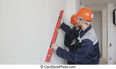 worker checking level of wall at construction site