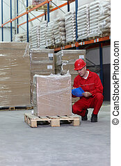 Crouching worker in red uniform checking specification of goods in box on wooden pallet