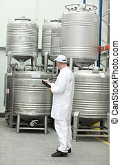 worker checking stocks in liquid foodstuff storehouse