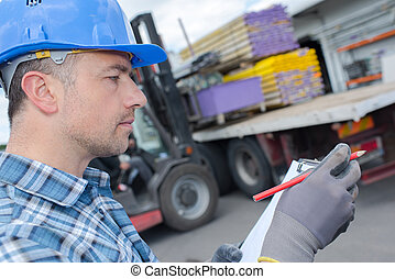 worker checking the delivery list