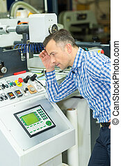 worker checking the quality of the printing
