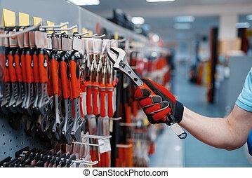 Worker choosing adjustable wrench in tool store