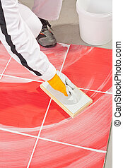 worker in white overalls clean with sponge trowel tile white joints grout and red tiles