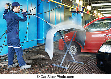 worker cleaning car bumper with pressured water - Repairman...