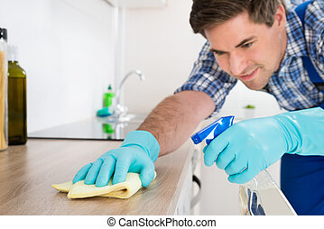 Worker Cleaning Countertop With Rag - Young Worker In...