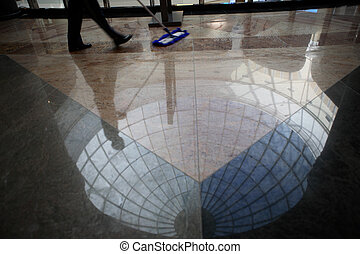 Worker cleaning floor - A worker cleaning the floor in an...