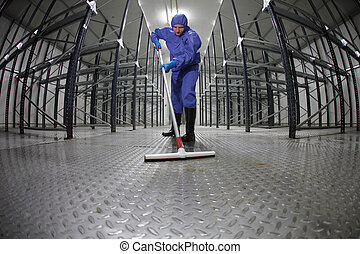 worker cleaning floor - storehouse - worker in protective...