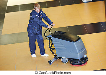 worker cleaning floor with machine