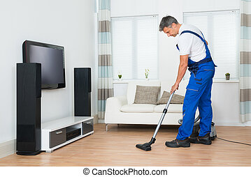 Worker Cleaning Floor With Vacuum Cleaner In Living Room