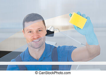 Worker Cleaning Glass With Rag - Mid adult male worker...