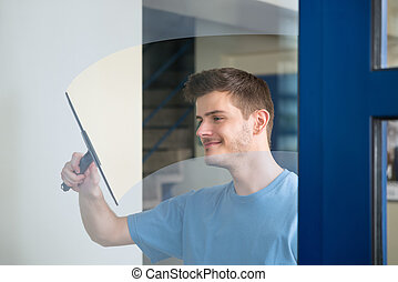 Worker Cleaning Glass With Squeegee - Young Male Worker...