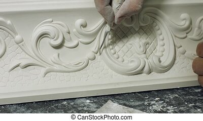 Worker cleaning gypsum ornament close up. Man working with...