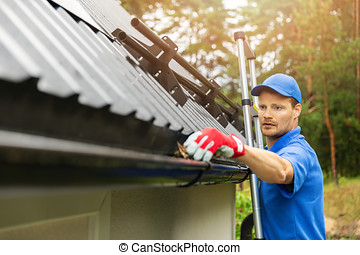 worker cleaning house gutter from leaves and dirt