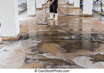Worker cleaning sand wash exterior walkway using polishing...