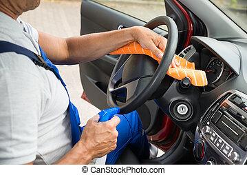 Worker Cleaning Steering Wheel Of Car