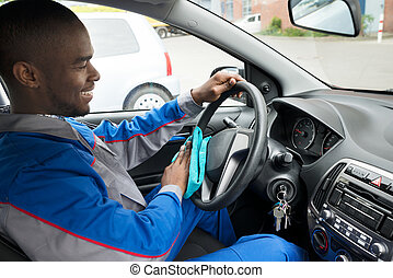 Worker Cleaning Steering Wheel Of Car With Cloth