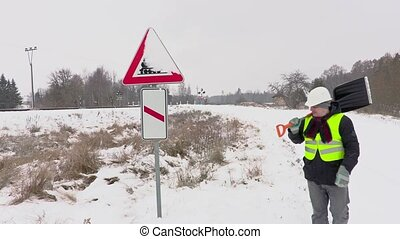 Worker cleaning warning sign from snow near road