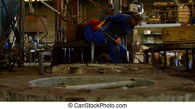 Worker cleaning with broom in foundry workshop 4k - Worker ...