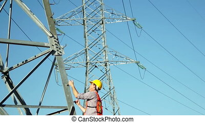Worker Climbs Electrical Tower - Technician in a safety vest...