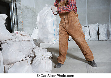 Worker collecting construction waste in bag