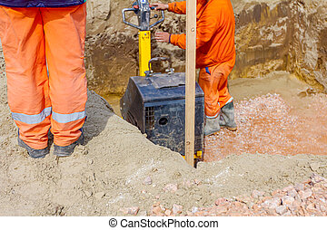 Worker compacting foundation using vibration plate compactor...
