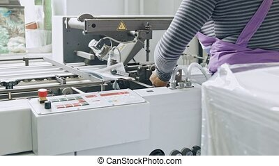Worker completes a paper for a magazine - manual labor at polygraph printing process
