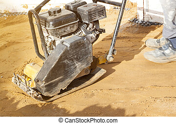 worker compresses sand in blind area around building with ...