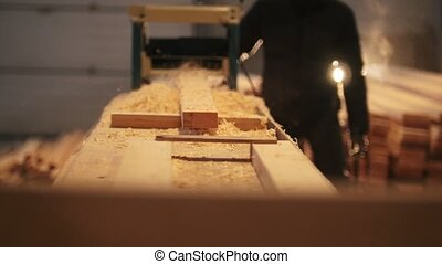 Worker control process of sawing a board at the sawmill,...