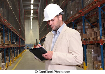 A worker counting the ready products stacked on the shelves in warehouse
