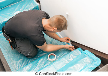 worker covering stairs carpet with masking film before home improvement works