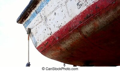 Worker covers metal with a primer paint of old rusty ship at...