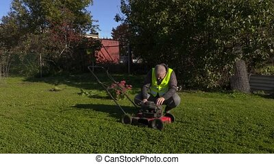 Worker cuts the grass