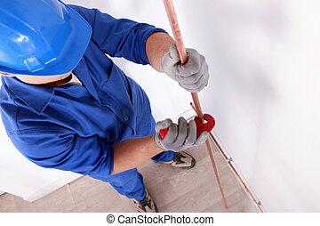 Worker cutting a copper tube