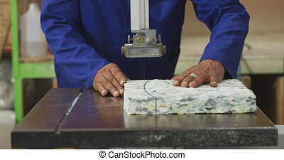 Worker cutting a piece of concrete block - Front view mid ...