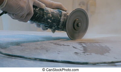 Worker cutting a tile using an angle grinder at construction...