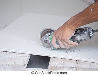 worker cutting a tile using an angle grinder