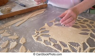 Worker cutting dough pieces with cookie cutter. Female baker cutting out leaves from cookie dough. Sugar cookie dough recipe.