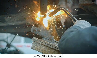 Worker cutting metal parts - Anonymous man using saw and...