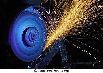 Worker cutting metal with grinder. Sparks while grinding ...