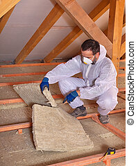 Worker cutting mineral wool panel to install thermal...