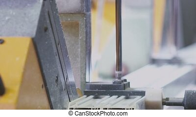 Worker cutting PVC profile with circular saw.