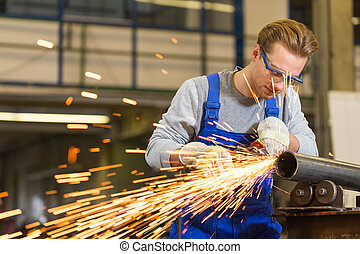 Worker cutting steel with angle grinder