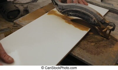 Worker cutting tiles on tile cutter