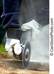 Worker cutting with an angle grinder