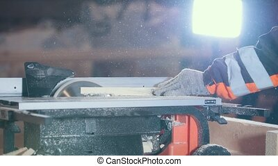 Worker cutting wooden plank with dangerous circular electric saw, profile view