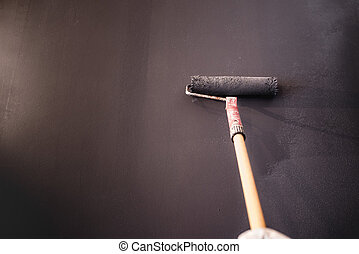 Worker decorating walls with grey paint. Construction plaster worker painting and renovating with professional tools